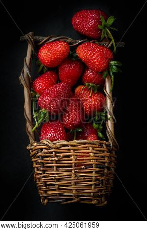 Ripe Red Strawberries Scattered From Wicker Basket On Dark Background