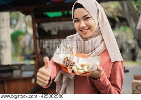Happy Customer Enjoying Chicken Satay And Showing Thumb Up