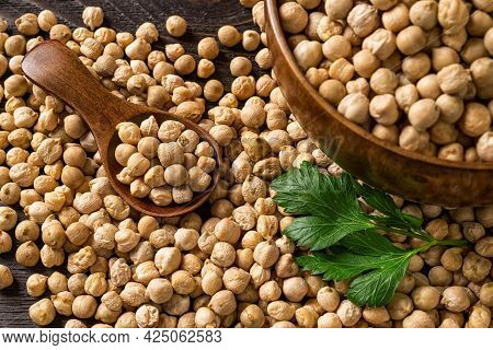 Raw Chickpeas In A Wooden Spoon On A Scattered Chickpea Beans Near A Wooden Bowl With Chick Peas On