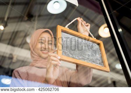 A Pretty Girl In A Headscarf Puts Up A Chalkboard On The Windowpane