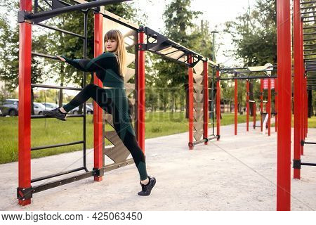 Sportive Young Woman In Sportswear Doing Leg Stretching On The Horizontal Bar On An Outdoor Sports F