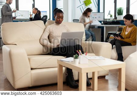 Concentrated Business Woman Reading News On Laptop, Sitting On Couch In Busy Start Up Company Office