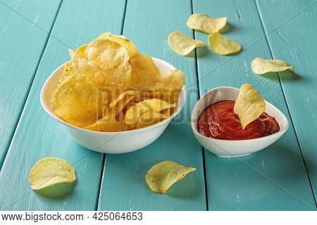 Delicious Potato Chips With Dill And Thick Tomato Ketchup In White Ceramic Bowls Over Blue Wooden Ta