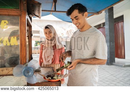 Street Food Seller With Walking Stall Of Indonesian Chicken Satay Cooking On A Hot Charcoal Grill