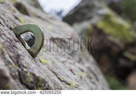 Bolt Or Parabolt Fixed Into A Hole Drilled In The Rock Full Of Lichen. Rock-climbing Equipment