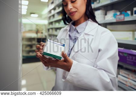 Beautiful Young Female Working In Chemist Wearing Labcoat Checking Medicine