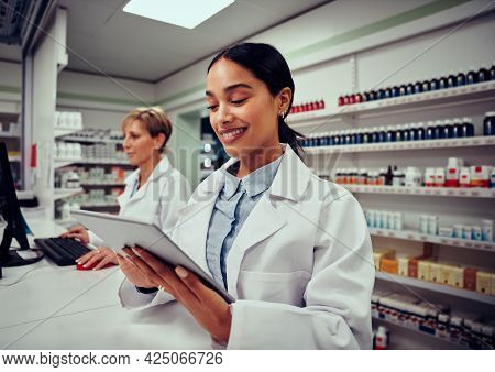 Happy Woman Working In Medical Store Wearing Labcoat Using Digital Tablet With Colleague Working In
