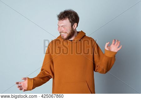 Portrait Of A Handsome Modern Man Who Laughs, Standing And Laughing Over Gray Background. True Human