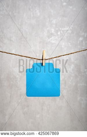 Blank Blue Paper Card Hang With Clothespin On Rope. Copy Space. Place For Your Text. Gray Background