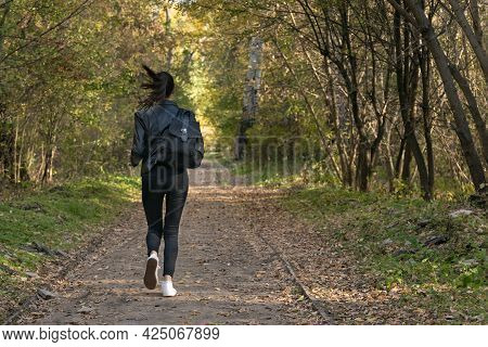 Girl Runs Along The Park Alley. Young Woman Runs Away From Someone In The Park. Lonely Girl In Fores