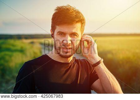 Man Preparing For Running At Sunset, Turning On Wireless Earphones. Portrait Of Caucasian Millenial