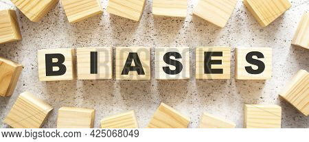 The Word Biases Consists Of Wooden Cubes With Letters, Top View On A Light Background. Work Space.