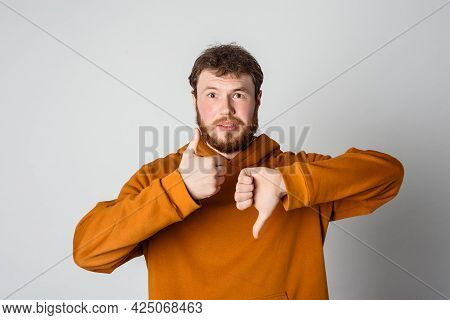 Handsome Man With Beard Doing Thumbs Up And Down, Disagreement And Agreement Expression, Standing In