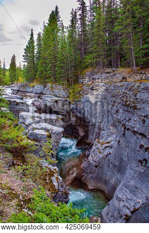 Maligne Canyon is the most unusual and interesting gorge in the Canadian Rockies. Travel to the Rocky Mountains. Cool cloudy day. The sheer canyon walls and the seething icy water below