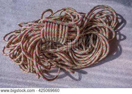Multi-colored Rock Climbing Ropes In Bundles. Macro Detail Of A Nylon Rope. Background Of The Coiled