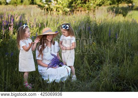 Russia, Yelabuga, June 18, 2021: A Mother With Her Twin Daughters On A Lawn Among Flowers. Laughing