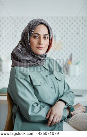 Vertical Portrait Of Confident Middle-eastern Woman Wearing Headscarf In Office And Looking At Camer
