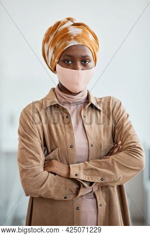 Vertical Waist Up Portrait Of Modern African-american Woman Wearing Mask And Looking At Camera While