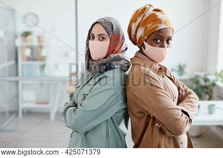 Waist Up Portrait Of Two Ethnic Young Women Standing Back To Back In Office And Looking At Camera, C
