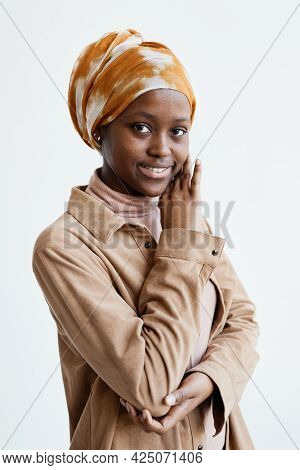 Vertical Waist Up Portrait Of Smiling African-american Woman Looking At Camera While Standing Agains