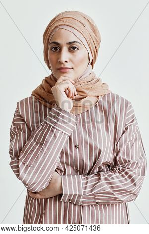 Vertical Waist Up Portrait Of Beautiful Middle-eastern Woman Looking At Camera And Wearing Headscarf