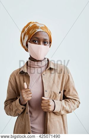 Vertical Waist Up Portrait Of Modern African-american Woman Wearing Mask And Looking At Mwhile Stand