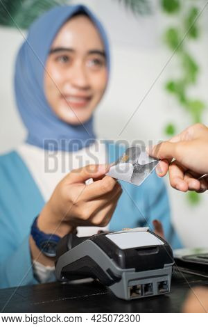 Close Up Of A Veiled Business Woman Smiles As She Returns Credit Cards To Customers While Paying Cas