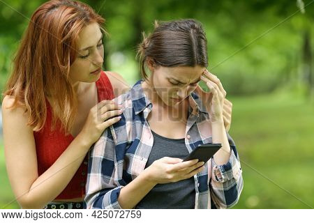 Sad Student Checking Smart Phone Being Comforted By A Friend In A Park Or Campus