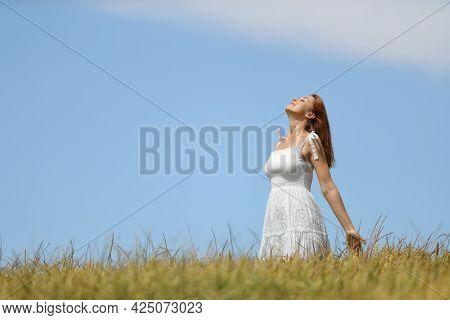 Happy Woman Wearing White Dress Breathing Fresh Air In A Wheat Field
