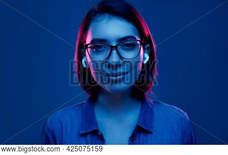 Positive Young Female In Stylish Eyeglasses Listening To Music Through True Wireless Earbuds And Loo
