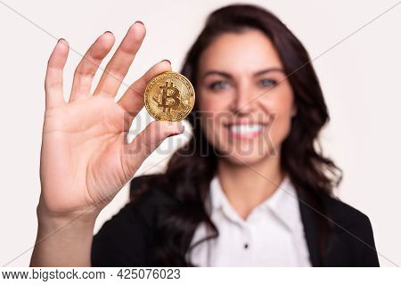 Optimistic Successful Female Investor Smiling And Demonstrating Golden Bitcoin Coin While Representi