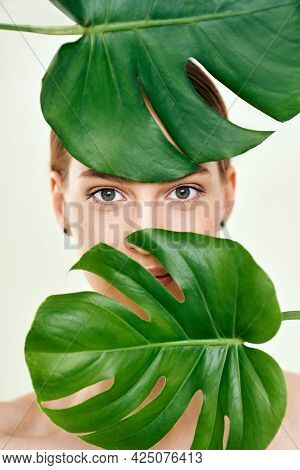Close Up Portrait Of Young Beautiful Woman With Perfect Smooth Skin Hiding In Tropical Leaves