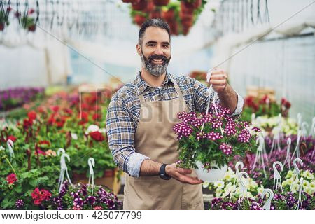 Mid Adult Man Is Owning Small Business Greenhouse Store.