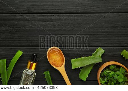 Aloe Vera Gel On Wooden Spoon With Aloe Vera And Oil Bottle On Black Wooden Background. Top View.