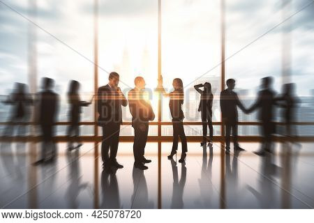 Successful Businessmen Hi-fiving In Blurry Office Interior With Sunlight. Success And Work Ethics Co