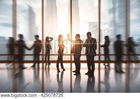Successful Businesspeople Hi-fiving In Blurry Office Interior With Sunlight. Success And Work Ethics