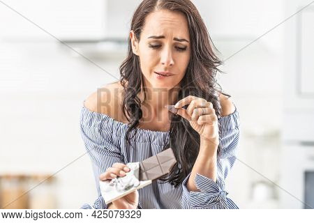 Guilty Expression Of A Woman Who Bites Off From A Chocolate Bar.
