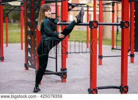 Athletic Young Woman In Tight Sportswear Doing Stretching With A Horizontal Bar On The Sports Area F