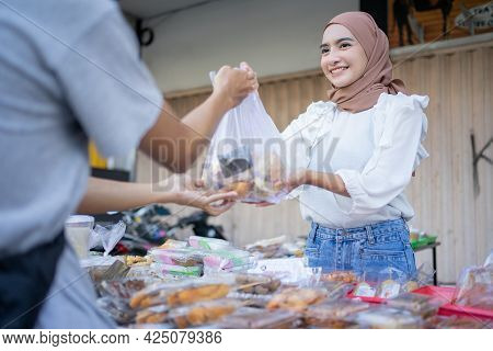 A Beautiful Girl In A Headscarf Gives A Takjil Food Order In A Plastic Bag To A Buyer