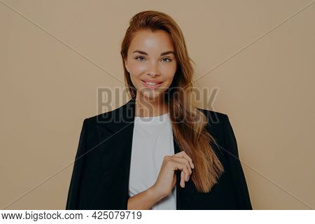 Friendly Smiling Brunette Businesswoman With Loose Long Hair, Wears Formal Black Jacket Over White B