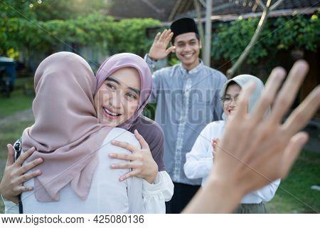 A Woman Wearing A Headscarf Hugs A Veiled Woman