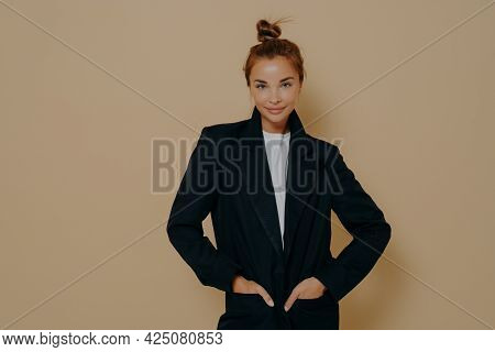 Attractive Young Model Female In Black Suit With Hair Tied Up In High Bun Posing With Her Hands In J