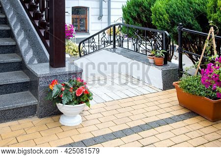 Flowerpots With Flowers At The Staircase Of The Front Porch Of The Building Faced With Granite Stone