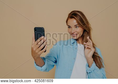 Pretty Young Woman Makes Selfie With Smart Phone, Dressed In Casual Clothes, Posing Against Beige Co