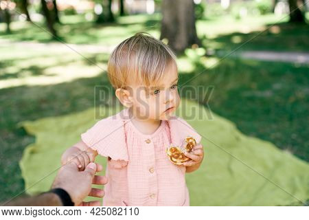 Little Girl Stands On A Green Lawn And Eats A Pancake