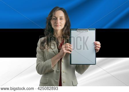 Study In Estonia Beautiful Woman Holding A Sheet Of Paper In Her Hands. Girl On The Background Of Th