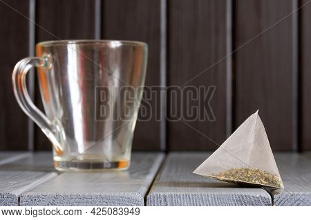 Pyramid Tea Bag With Green Tea Lies On Vintage Table Made Of Natural Wooden Boards Next To Transpare