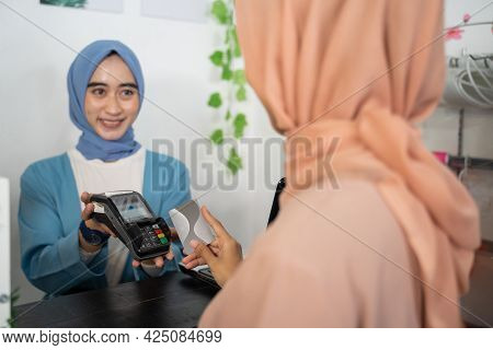 A Smiling Veiled Business Woman Holds An Edc Machine While A Customer Holds A Credit Card While Payi