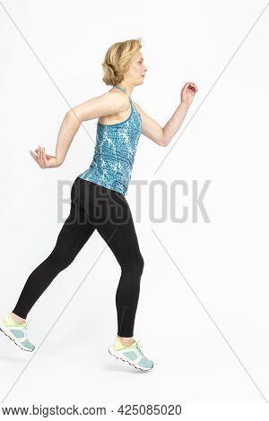 Women Sport Ideas. Running Fitness Mature Sportswoman During Active Jogging Training Against White B