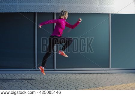 Mature Woman Running In High Jump Outdoors Against Glass Reflective Background.